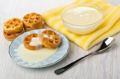 Waffles macios com leite condensado nos pires, bacia com leite condensado no guardanapo, colher na tabela de madeira fotografia de stock
