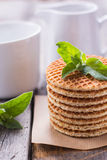 Waffles with peppermint and tea with milk for breakfast. Waffles with peppermint and tea with milkn Royalty Free Stock Images