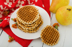Waffles on a plate with pears and red cloth. Horizontal view Royalty Free Stock Photo