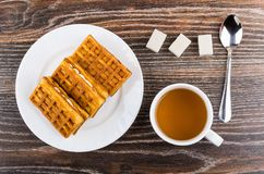 Waffles in plate, sugar cubes, teaspoon and cup of tea. Waffles in white plate, sugar cubes, teaspoon and cup of tea on wooden table. Top view Royalty Free Stock Images
