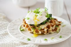 Waffles with poached egg and flowing yolk, cheese and spinach. For healthy breakfast stock photos