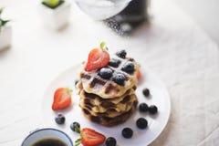 Waffles que estão sendo polvilhados com o açúcar Imagem de Stock Royalty Free