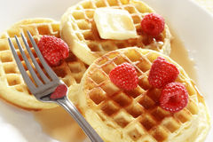 Waffles and raspberries. With a fork on a plate with syrup and butter Stock Photos