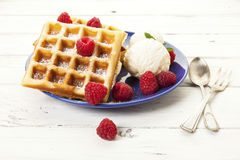 Waffles, raspberries, ice cream on blue plate royalty free stock photography
