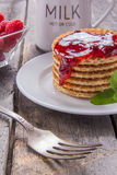 Waffles with raspberries and jam for breakfast on a wooden table. Waffles with raspberries and jam for breakfast Stock Photos