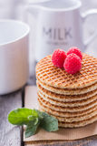 Waffles with raspberries and milk tea for breakfast on a wooden. Waffles with raspberries and milk tea for breakfast Royalty Free Stock Photo