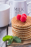 Waffles with raspberries and milk tea for breakfast on a wooden. Table Royalty Free Stock Photos