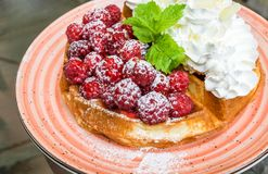 Waffles with raspberries and whipped cream. Tasty belgian waffles with fresh raspberries and whipped cream with almond flakes. Decorated with mint leaves and Stock Photo
