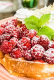 Waffles with raspberries and whipped cream. Tasty belgian waffles with fresh raspberries and whipped cream with almond flakes. Decorated with mint leaves and Stock Photography