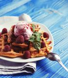 Waffles with raspberry ice cream and fresh raspberries, decorate. D with mint over blue wooden background, close up Stock Image