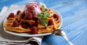 Waffles with raspberry ice cream and fresh raspberries, decorate. D with mint over blue wooden background, close up Stock Photography