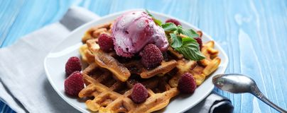 Waffles with raspberry ice cream and fresh raspberries, decorated with mint over blue wooden background. Close up Royalty Free Stock Image