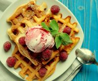 Waffles with raspberry ice cream and fresh raspberries, decorated with mint over blue wooden background, close up. Waffles with raspberry ice cream and fresh Stock Images