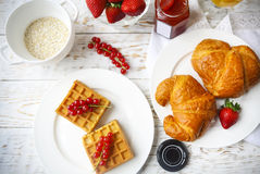 Waffles with red currant jam and berries, croissants, orange jui. Waffles with red currant jam and berries on a white plate, croissants, orange juice and oat Stock Image