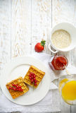Waffles with red currant jam and berries, orange juice and oat f. Waffles with red currant jam and berries on a white plate, orange juice and oat flakes oatmeal Royalty Free Stock Images