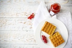 Waffles with red currant jam and berries on a white plate. On the wooden background Stock Images