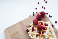 Waffles with red frozen strawberry. On a wooden breadboard. Red, white, beige colours. Strawberry and cowberry stock photography