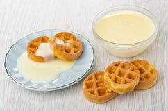 Waffles redondos macios com leite condensado nos pires, bacia com leite condensado na tabela fotos de stock