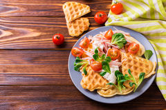 Waffles sandwich with bacon, cherry tomatoes and corn salad royalty free stock image