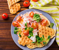 Waffles sandwich with bacon, cherry tomatoes and corn salad. Waffles sandwich with bacon, ham, cherry tomatoes and fresh corn salad on wooden table. Breakfast Royalty Free Stock Photo