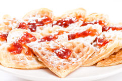 Waffles in shape of heart with strawberry jam. Stack of waffles in shape of heart with strawberry jam and powdered sugar on plate Royalty Free Stock Images