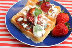 Waffles. Some waffles with cream, honey and strawberries stock images