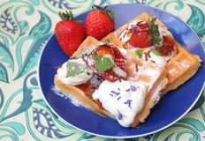 Waffles. Some waffles with cream and strawberries royalty free stock images