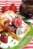 Waffles. Some waffles with cream and strawberries royalty free stock photography
