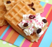 Waffles. Some homemade waffles with cream and raisins royalty free stock photo