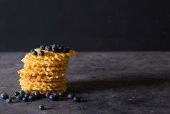 Waffles. Stack Belgian waffles with blueberries on a dark gray background. Sweet food concept. Copy space. Fresh blueberries Stock Photos