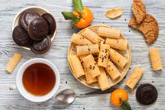Waffles a straw in a plate with tea and chocolate biscuits on a wooden white table. stock images