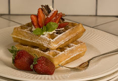 Waffles and Strawberries. Belgium waffles topped with whipped cream, fresh strawberries, shaved chocolate, and dusted with confectioners sugar stock photo