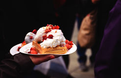 Waffles with strawberries and cream. A person holding two plates with waffles, strawberries and cream during the Festa Frawli, an annual strawberry festival held Stock Images