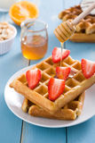 Waffles with strawberries and honey royalty free stock photography