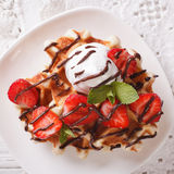 Waffles with strawberries, whipped cream and chocolate closeup. Royalty Free Stock Photography