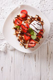 Waffles with strawberries, whipped cream and chocolate closeup. Royalty Free Stock Images