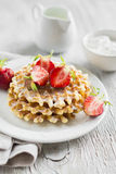 Waffles with strawberries on a white plate Stock Images