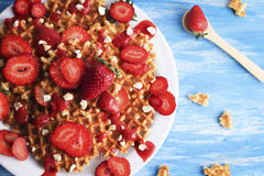 Waffles with strawberry on white plate on blue background. Top view flat lay Royalty Free Stock Photography