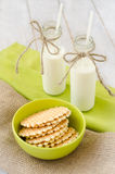 Waffles and two bottles of milk. Waffles in a ceramic bowl on a sackcloth with two bottles of milk on a green table napkin Royalty Free Stock Photos