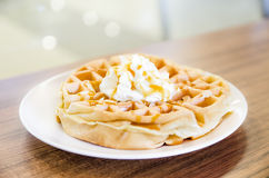 Waffles under the caramel topping with cream on top Royalty Free Stock Photos