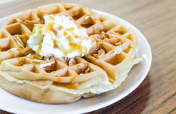 Waffles under the caramel topping with cream on top Stock Photos