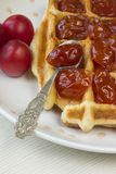 Waffles. With jam from a plum on a white plate Stock Images