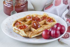 Waffles. With jam from a plum on a white plate Royalty Free Stock Photography