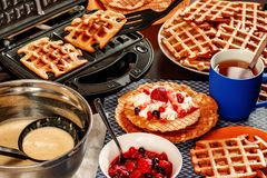 Waffles with whipped cream, berries and tea. Waffles are fried from dough in a waffle maker royalty free stock photography