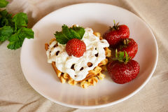 Waffles with whipped cream and strawberries. Selective focus Royalty Free Stock Photo