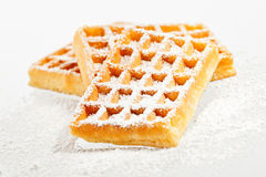 Waffles on a white background. Sugared waffles on a white background royalty free stock images