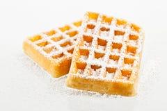 Waffles on a white background. Sugared waffles isolated on a white background royalty free stock image