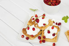 Waffles with wild strawberries and whipped cream royalty free stock image