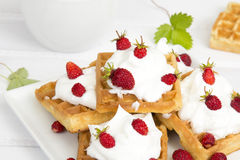 Waffles with wild strawberries and whipped cream Stock Photo