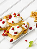 Waffles with wild strawberries and whipped cream on white table Stock Photo